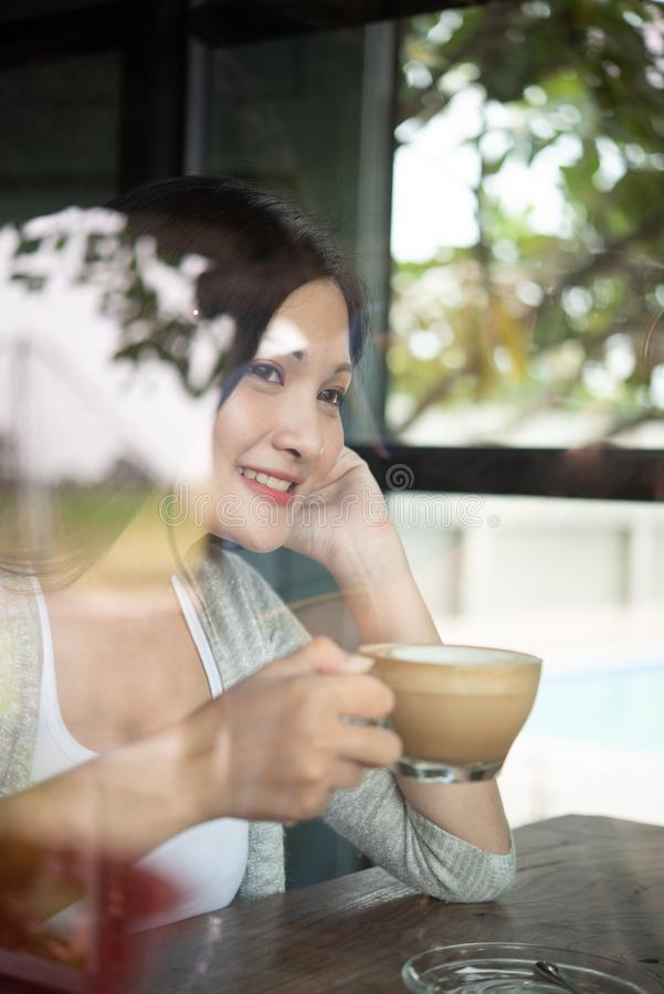Een mooie Aziatische vrouw glimlacht gelukkig met koffie in het restaurant Levensstijl van jonge vrouwen tijdens de ontspannende  royalty-vrije stock foto