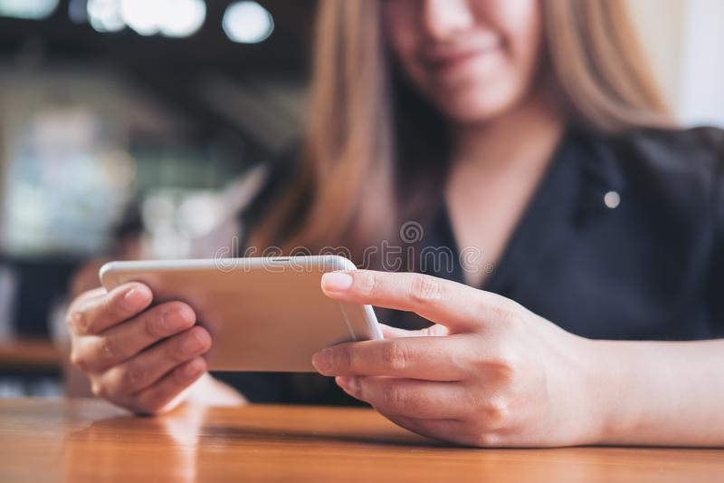 Een mooie Aziatische vrouw met smileygezicht die en horizontale slimme telefoon houden met behulp van aan het letten op TV en het stock afbeelding