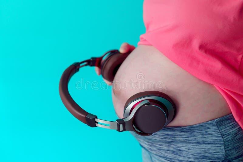 Een mooie Aziatische vrouw is zwanger Dragend een roze overhemd neem een grote hoofdtelefoon komen aan de maag laten het kind in  royalty-vrije stock afbeelding