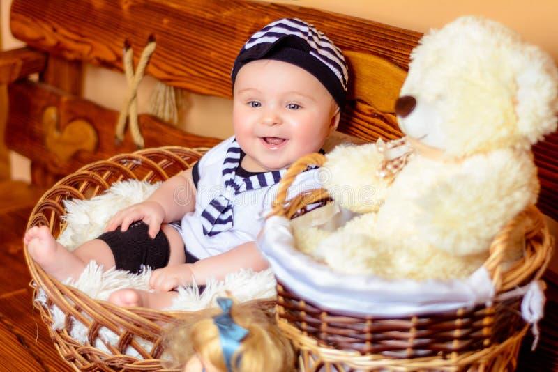 Een mooie baby in een zeeliedenkostuum zit in een mand naast een pluche draagt stock fotografie