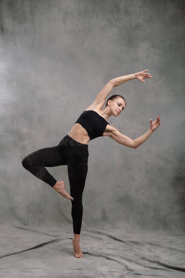 Een mooie bevallige slanke vrouwendanser in zwarte kleren voert choregrafische cijfers en bewegingen van moderne dans uit en royalty-vrije stock foto