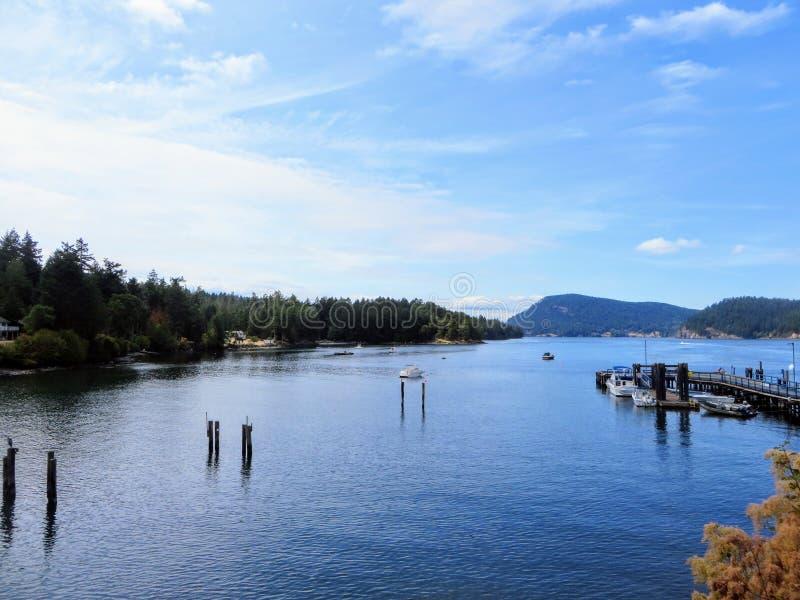 Een mooie blauwe baai met houten steigers en een dok met boten omringd door boseilanden op Mayne Island, British Columbia stock foto's