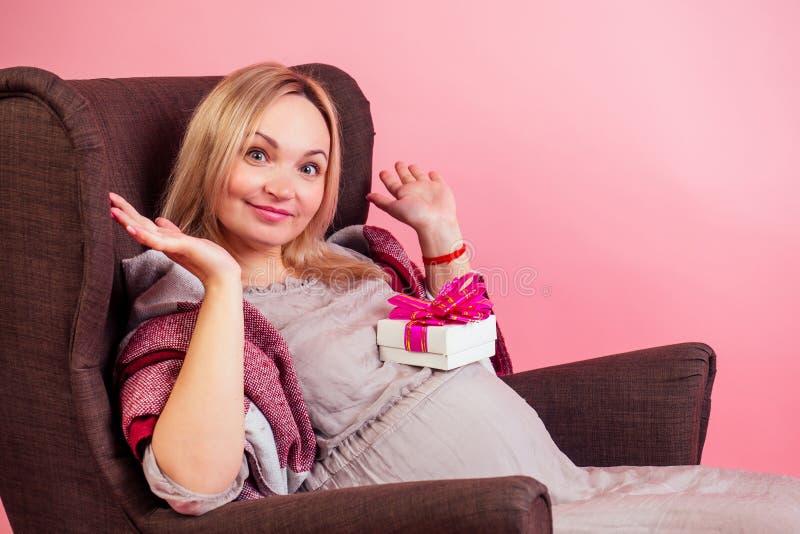 Een mooie blonde, smiley zwangere vrouw, een grote babyschoen die in een comfortabele stoel zit, bedekt met een warme deken, kree royalty-vrije stock afbeeldingen