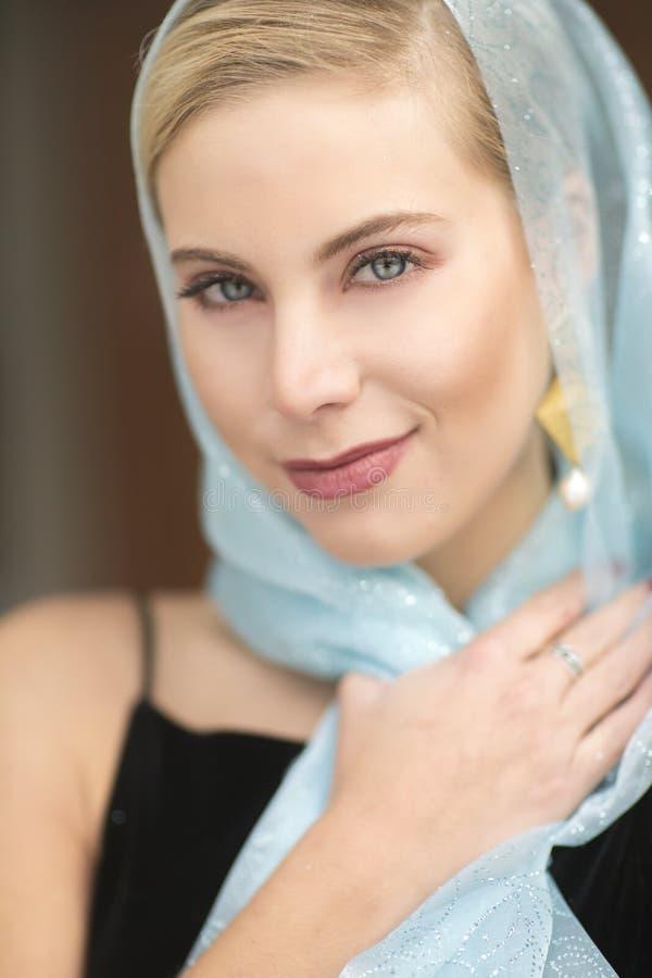 Een mooie blonde vrouw met een glittery blauwe sjaal en een zwarte kleding stock afbeeldingen