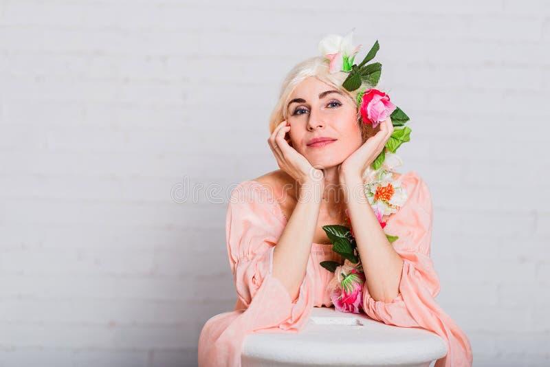 Een mooie broedende vrouw vouwde haar handen onder haar kin kunstbloemen in haar haar stock foto's