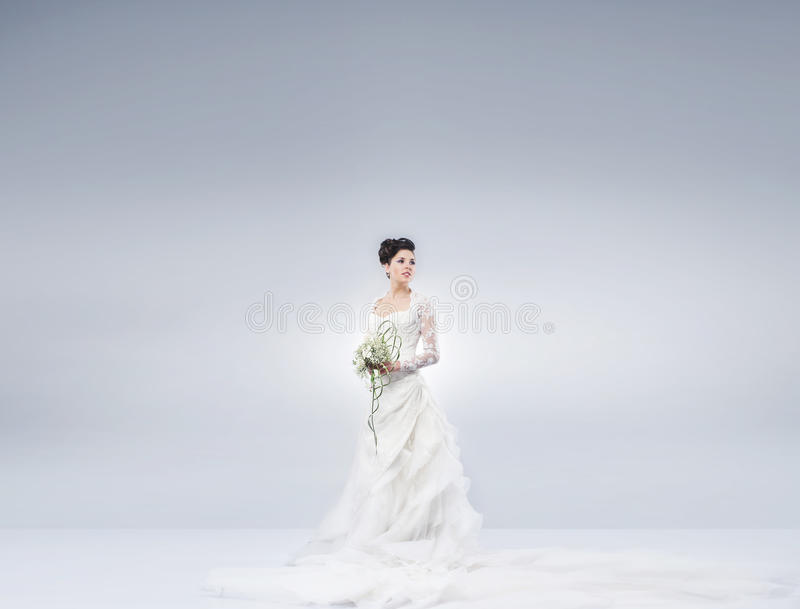 Een mooie bruid die zich met een bloemboeket bevinden stock afbeelding