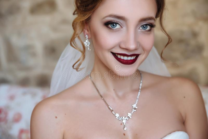 Een mooie bruid en een kleding met open schouders Een close-up van een meisje met een gevoelige oogmake-up en rode lippen wordt g royalty-vrije stock afbeeldingen