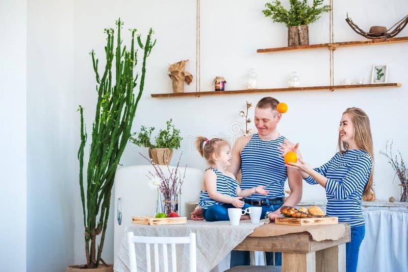 Een mooie de lentefoto van een gelukkige familie in blauwe de zomervesten binnen de keuken in lichte geweven kleuren met een ol royalty-vrije stock foto's