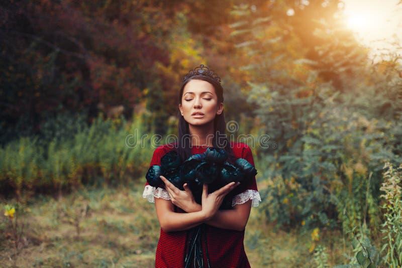 Een mooie donker-haired prinses in een zwarte kroon koestert dode bloemen Vloek, Verhaal van een Meisje en Dode Rozen stock foto