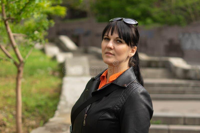 Een mooie donkerbruine vrouw in een zwart jasje en een oranje overhemd stelt binnen tegen de achtergrond van een lange concrete t stock foto