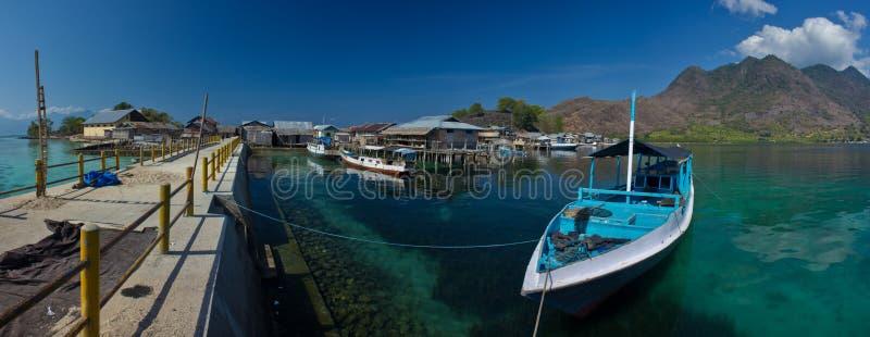 Een mooie en verbazende portretscène op de kust van Flores met een traditionele boot als voorgrond en berg en visser royalty-vrije stock afbeelding