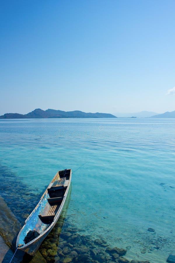 Een mooie en verbazende portretscène op de kust van Flores met een traditionele boot als voorgrond en Flores-eilanden zoals stock fotografie