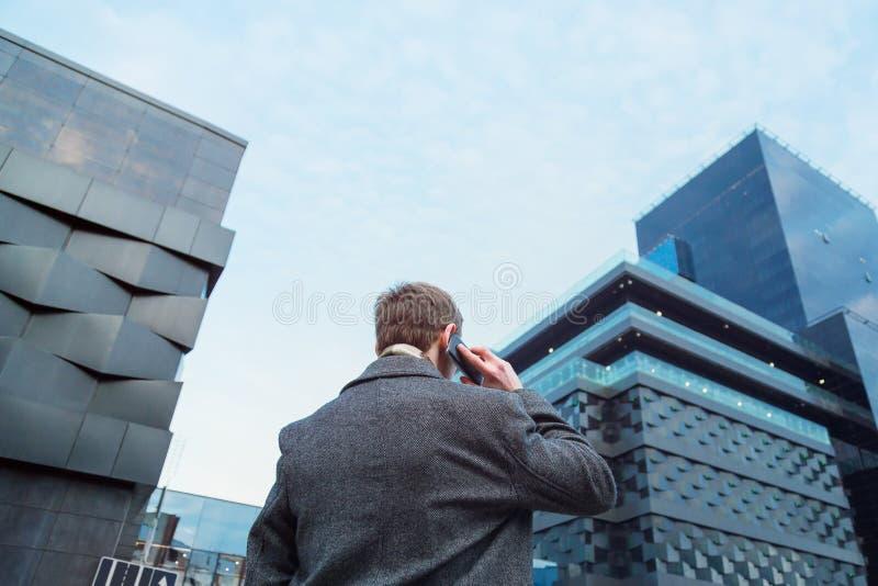 Een mooie geklede mens die op een mobiele telefoon voor een bureauwolkenkrabber spreken Mening van de rug van beneden naar boven royalty-vrije stock fotografie