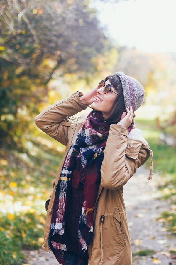 Een mooie gelukkige glimlachende jonge vrouw in het de herfstpark stock foto's