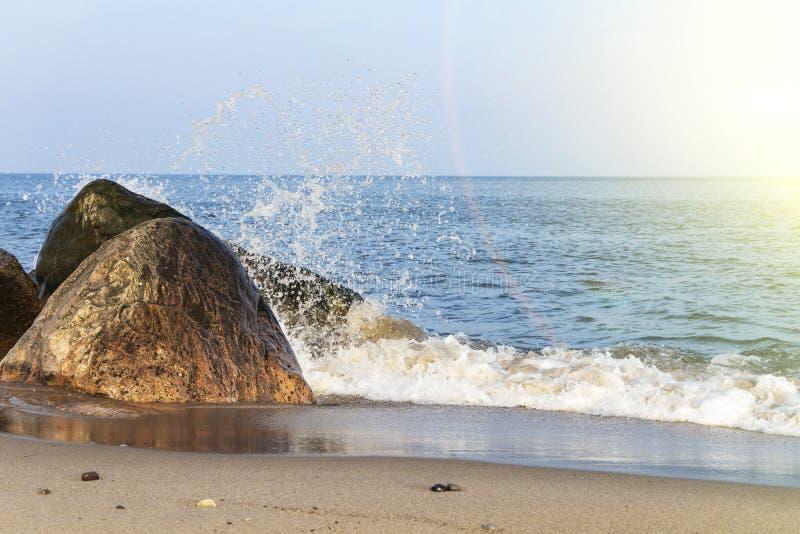 Een mooie golf raakt de rotsen op een zandig strand op een Zonnige dag stock foto