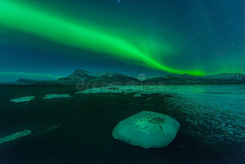 Een mooie groene en rode dageraad over de Jokulsarlon-lagune, IJsland stock fotografie