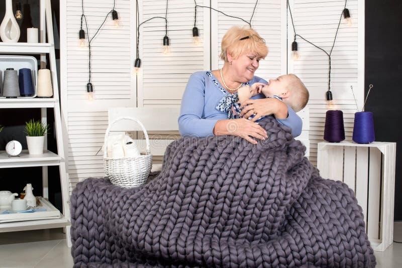 Een mooie grootmoeder en een kleinzoon zitten op de bank onder een gebreide algemene merinoswol en de offerte omhelst Een gelukki royalty-vrije stock foto