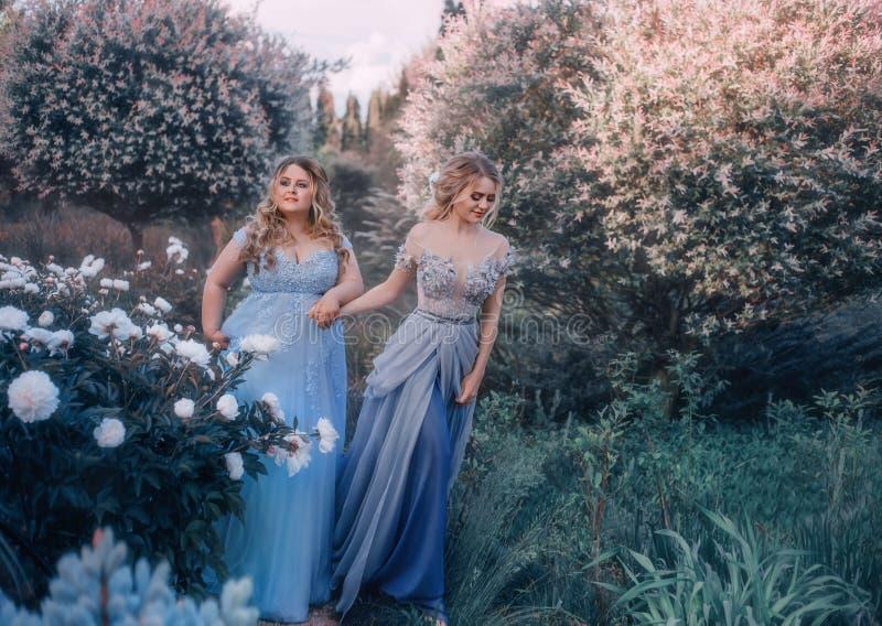 Een mooie grote vrouw houdt een breekbaar blondemeisje in haar hand Twee prinsessen in luxueuze blauwe kleding tegen stock foto's