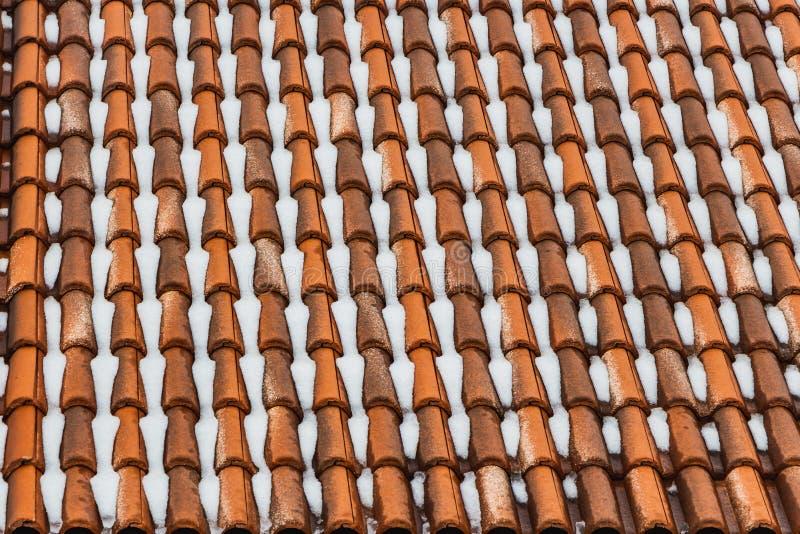 Een mooie horizontale textuur van een deel van een oud nat bruin dak van kleitegels met witte sneeuw in de winter stock afbeeldingen