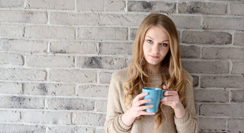 Een mooie jonge blondevrouw het drinken koffie van Cu stock fotografie