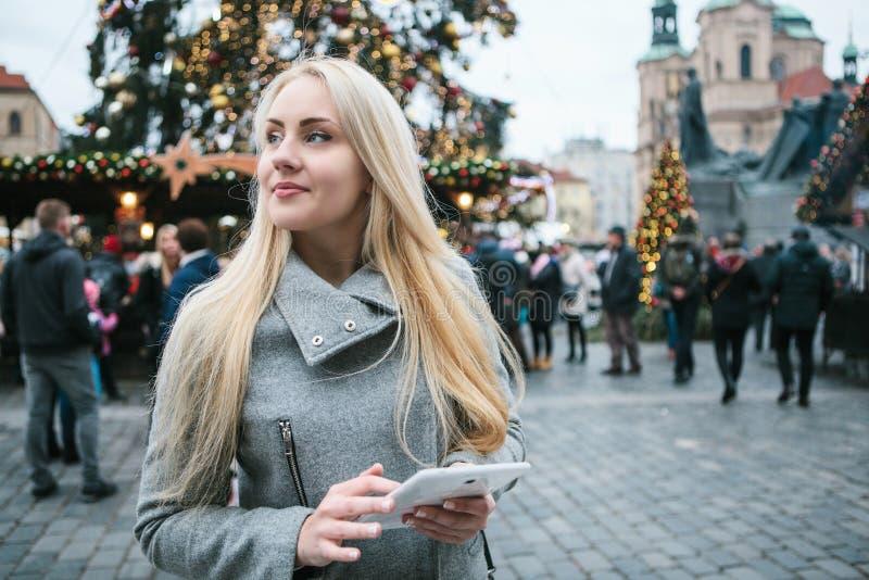 Een mooie jonge blondevrouw of een toerist gebruiken een tablet royalty-vrije stock fotografie