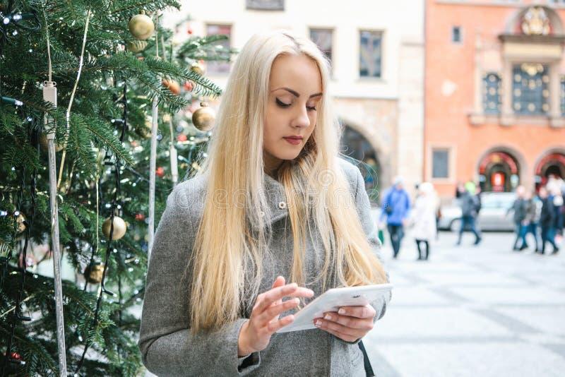 Een mooie jonge blondevrouw of een toerist gebruiken een tablet stock fotografie