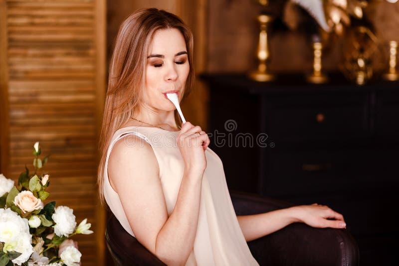 Een mooie jonge glimlachende vrouw in een beige kleding likt een kleine lepel met genoegen royalty-vrije stock foto