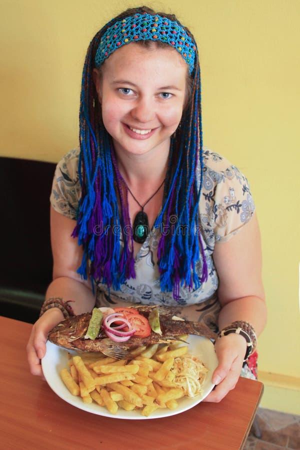 Een mooie jonge Kaukasische vrouw met blauwe ogen glimlacht en houdt een Ugandan traditioneel voedsel - Tilapia vissen van Meerka stock fotografie
