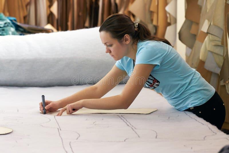 Een mooie jonge meisjeskleermaker die met een scherp binnen materiaal werken stock afbeeldingen