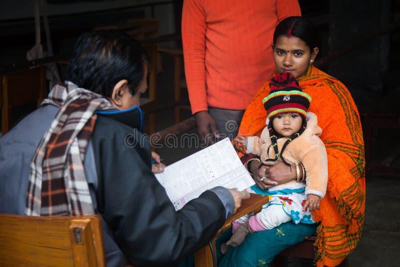 Een mooie jonge moeder is met haar kind arts komen zien stock afbeeldingen