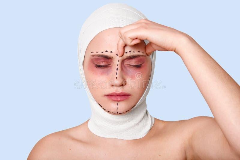 Een mooie jonge vrouw bevindt zich tegen blauwe muur met verband op haar hoofd Het meisje lijdt aan vreselijke hoofdpijn De dame  stock afbeeldingen