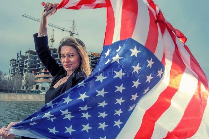 Een mooie jonge vrouw die een Amerikaanse vlagvlieg houden door wind stock fotografie