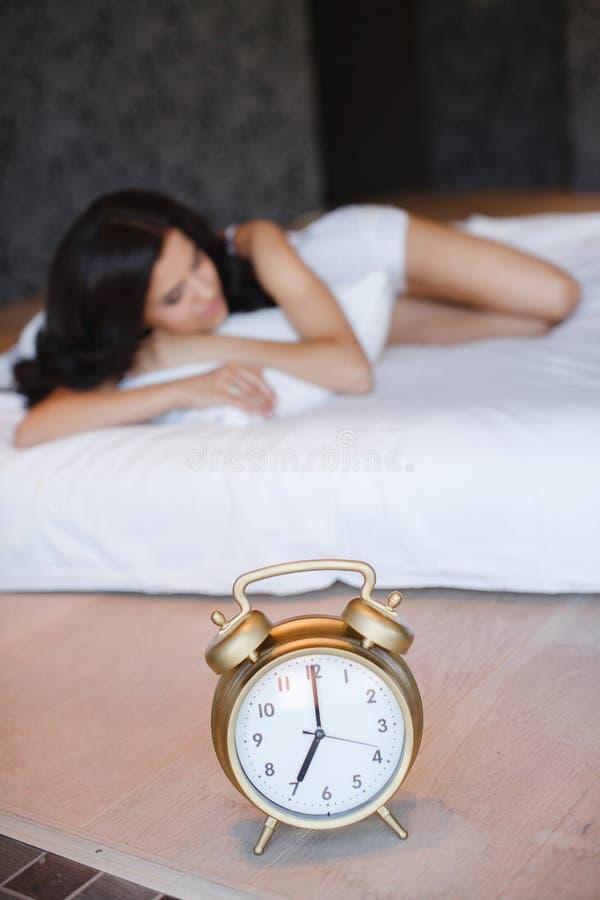 Een mooie jonge vrouw, die in bed thuis slapen stock afbeeldingen