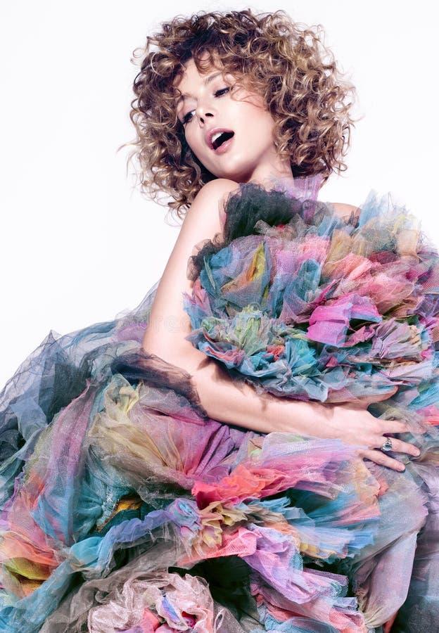 Een mooie jonge vrouw en een verscheidenheid van kleurrijke stoffen Leuk krullend haar royalty-vrije stock afbeelding