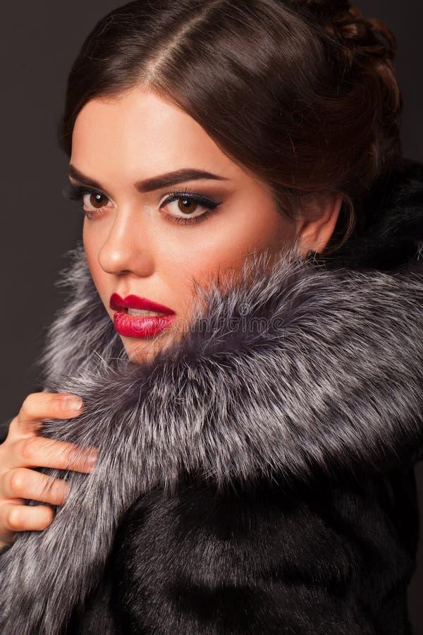 Een mooie jonge vrouw kleedde zich in een de winterlaag stock afbeeldingen