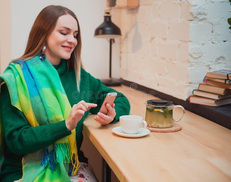 Een mooie jonge vrouw met blond haar zit in een koffie winkel Online Winkelend Zij drinkt heerlijke thee royalty-vrije stock foto's