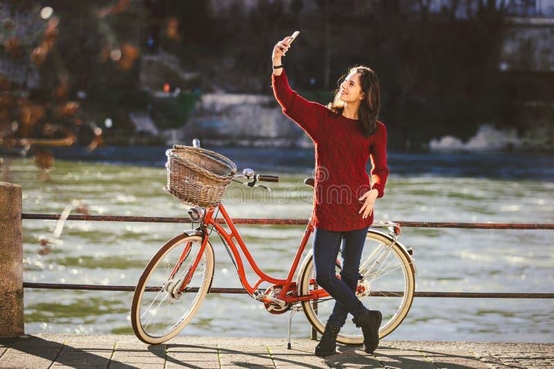Een mooie jonge vrouw met een retro rode fiets maakt een foto van zich in de oude stad van Europa op de Rivier Rijn embankm royalty-vrije stock afbeelding