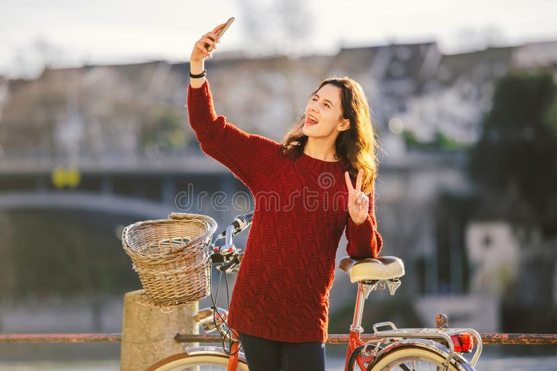 Een mooie jonge vrouw met een retro rode fiets maakt een foto van zich in de oude stad van Europa op de Rivier Rijn embankm stock foto