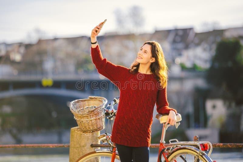 Een mooie jonge vrouw met een retro rode fiets maakt een foto van zich in de oude stad van Europa op de Rivier Rijn embankm stock fotografie
