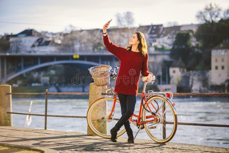 Een mooie jonge vrouw met een retro rode fiets maakt een foto van zich in de oude stad van Europa op de Rivier Rijn embankm stock foto's