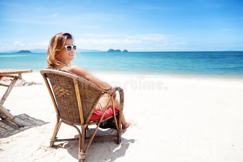 Een mooie jonge vrouw in een witte bikini zit op een tropische bea royalty-vrije stock afbeeldingen
