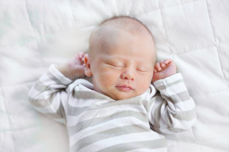 Een mooie jongen van de slaap pasgeboren baby op een witte deken Hij is stock foto's