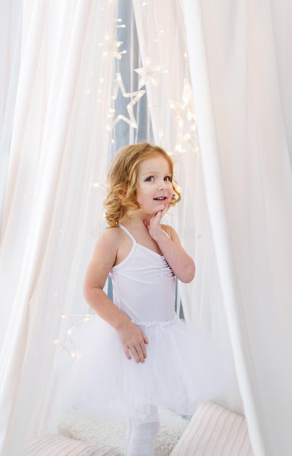 Een mooie kleine ballerina in witte kleding bevindt zich dichtbij het witte gordijn royalty-vrije stock foto