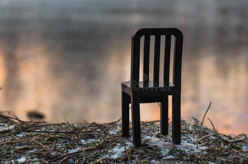Een mooie kleine stuk speelgoed zwarte plastic stoel is tribunes op gras met sneeuw door een vijver met bezinningen van een helde royalty-vrije stock foto's