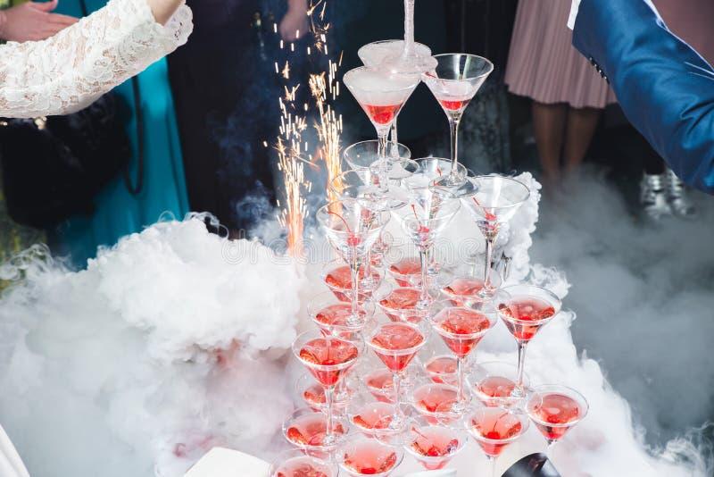 Een mooie lijst die met lege of volledige glazen wijn of champagne plaatsen die zich bovenop elkaar als dia of driehoek bevinden royalty-vrije stock afbeelding