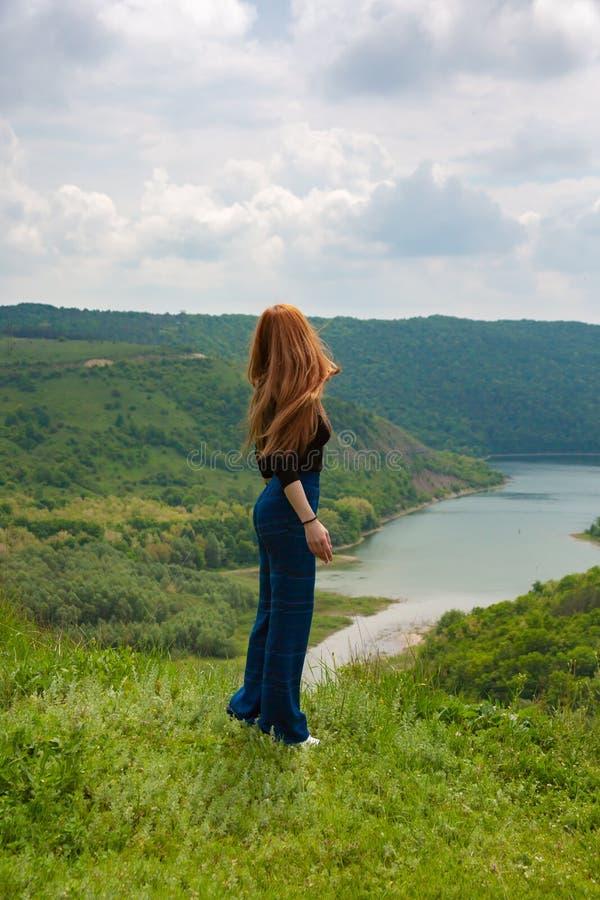 Een mooie meisjestoerist geniet van aard naast een bergrivier stock fotografie