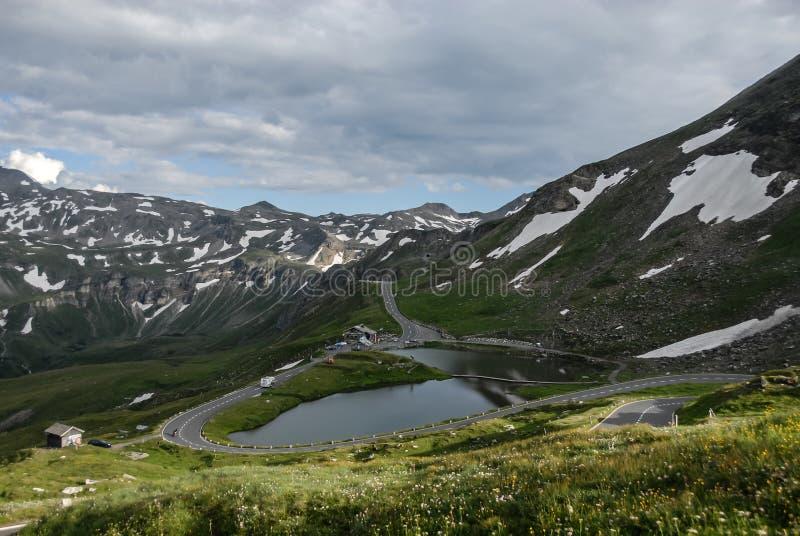 Een mooie mening van het meer, de weide en de hoogste opgedoken bergweg in de Hoge Alpiene Weg van Oostenrijk - van Grossglockner royalty-vrije stock afbeeldingen
