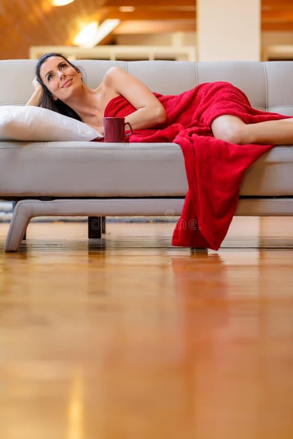 Een mooie naakte vrouw verpakte in het comfortabele algemene ontspannen op royalty-vrije stock fotografie