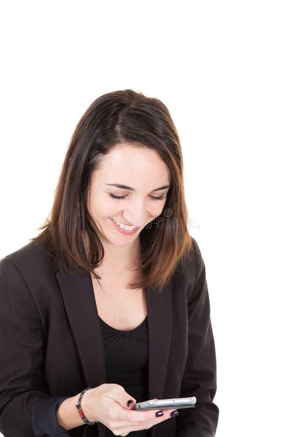 Een mooie onderneemster bekijkt haar mobiele telefoon op witte achtergrond stock foto's