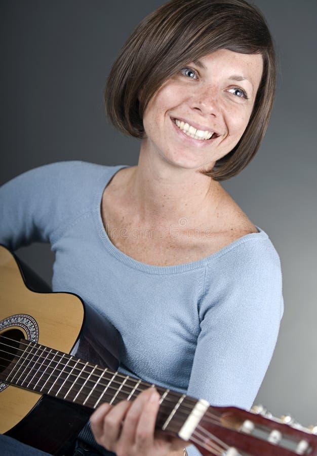 Een mooie rijpe gitaar van vrouwenspelen royalty-vrije stock afbeelding